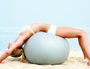 Фитнес-упражнения с мячом на пляже. Фото